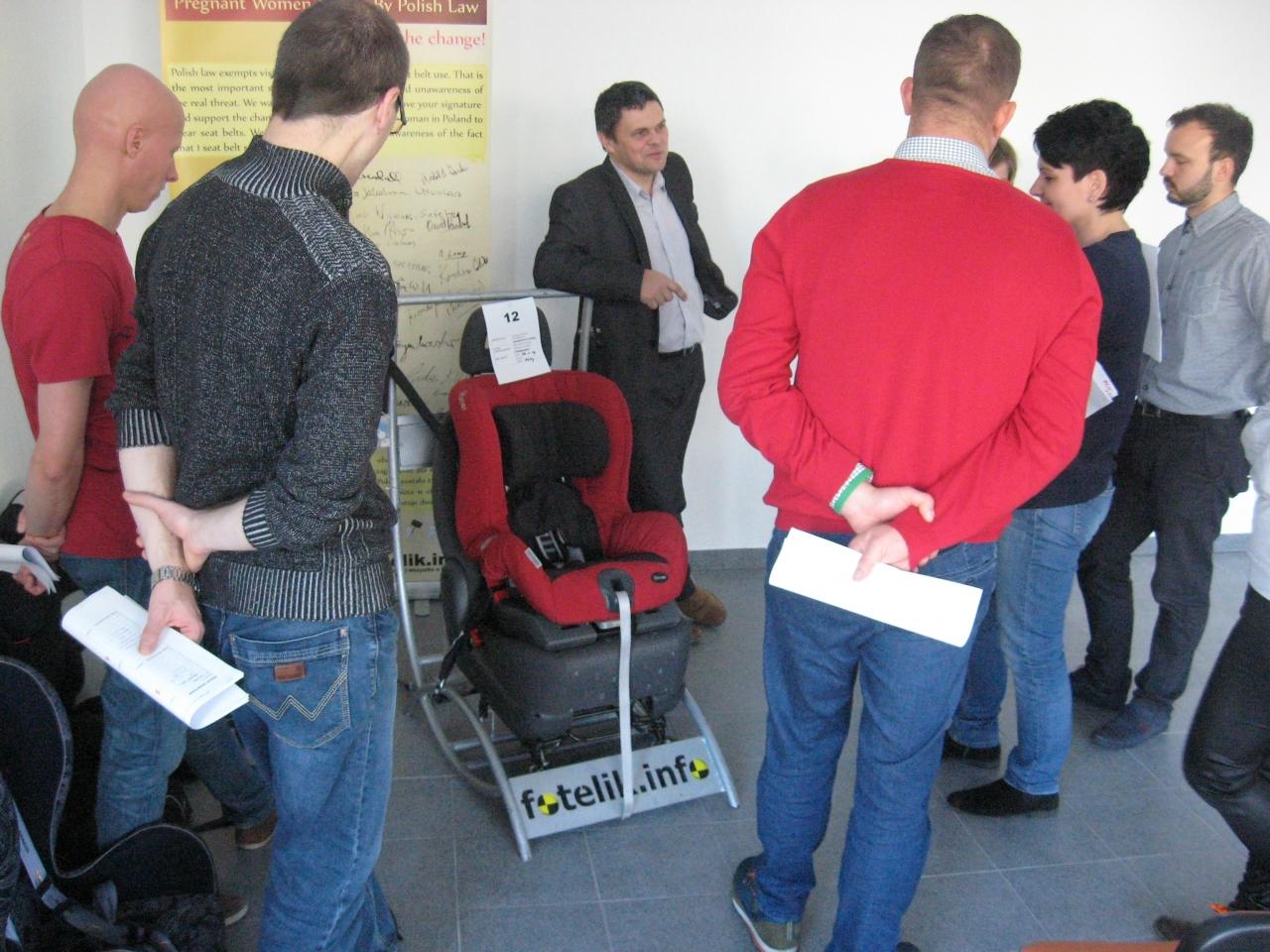 Uczestnicy słuchają i przyglądają się jakie błędy zostały popełnione przy montowaniu tego fotelika