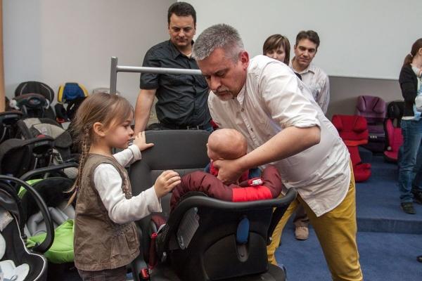 Paweł Zawitkowski pokazywał jak wkładać i wyjmować niemowlaka do i z fotelika